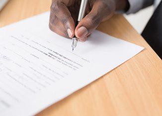 La main d'un homme tenant une plume prêt à signer un document.